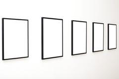 Vijf lege frames op witte muurtentoonstelling stock afbeeldingen