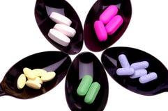 Vijf lepels met pillen stock foto's