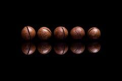 Vijf macadamia noten op zwarte weerspiegelende achtergrond royalty-vrije stock afbeelding
