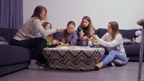 Vijf meisjes die zich rond de lijst verzamelen en met eetstokjes Aziatisch voedsel eten stock video