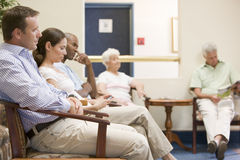 Vijf mensen die in wachtkamer wachten Stock Fotografie