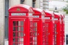 Vijf Rode telefooncellen allen van Londen op een rij Stock Fotografie