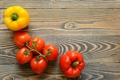 Vijf rode tomaten en Spaanse peper op een houten achtergrond Stock Afbeelding