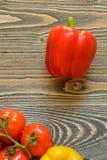 Vijf rode tomaten op een groene tak en Spaanse peper op een houten achtergrond Stock Foto