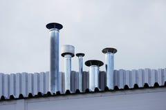 Schoorsteenpijp van roestvrij staal op het dak van het huis stock