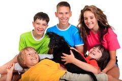 Vijf siblings met zwarte hond Stock Foto's