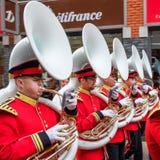 Vijf sousaphoneblazers in mooie rode opgestelde uniformen het marcheren in de stad stock foto