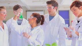 Vijf studenten die onderzoek naar installaties in laboratorium doen stock footage