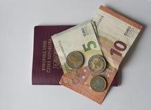 Vijf tien eurobankbiljet en twee één euro muntstuk op de EU-pa's royalty-vrije stock fotografie