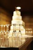 Vijf tiered huwelijkscake met lege champagnefluiten op lijst Stock Afbeelding