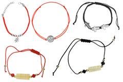 Vijf verschillende kleuren textielarmbanden met halfedelstenen en charmes van diverse die kleuren, op witte achtergrond worden ge royalty-vrije stock fotografie