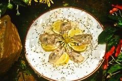 Vijf, verse, gepelde oesters met citroenplakken stock foto's