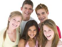 Vijf vrienden die samen glimlachen Stock Fotografie