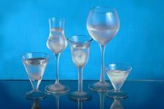 Vijf wijnglazen met ijs en water Stock Afbeelding