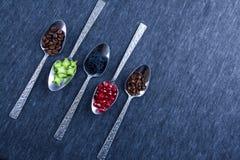 Vijf zilveren lepels met voedsel en kruiden Stock Afbeeldingen
