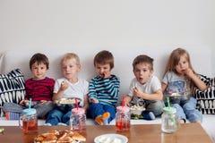 Vijf zoete jonge geitjes, vrienden, zittend in woonkamer, het letten op TV Royalty-vrije Stock Fotografie