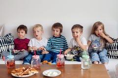 Vijf zoete jonge geitjes, vrienden, zittend in woonkamer, het letten op TV Royalty-vrije Stock Foto