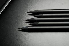 Vijf zwarte potloden over zwarte Royalty-vrije Stock Afbeeldingen