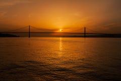 vijfde van April Bridge op Tagus-Rivier bij Zonsondergang Stock Foto