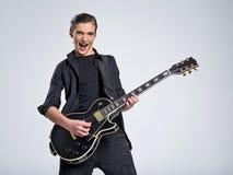 Vijftien jaar oude gitarist met een zwarte elektrische gitaar De tienermusicus houdt gitaar stock fotografie