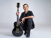 Vijftien jaar oude gitarist met een zwarte elektrische gitaar royalty-vrije stock afbeelding