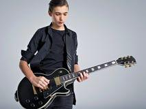 Vijftien jaar oude gitarist met een zwarte elektrische gitaar De tienermusicus houdt gitaar stock afbeeldingen