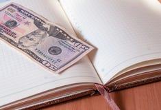 Vijftig Amerikaanse dollars en Blocnote op houten lijst Royalty-vrije Stock Afbeeldingen