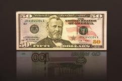 Vijftig dollars met bezinning honderd Russische roebels Stock Fotografie