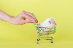 Vijftig euro in de het winkelen handkar, gele achtergrond Stock Foto's