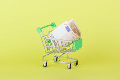 Vijftig euro in de het winkelen handkar, gele achtergrond Royalty-vrije Stock Afbeeldingen