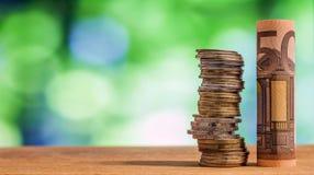 Vijftig euro gerold rekeningsbankbiljet, met euro muntstukken op groene blurre Stock Afbeelding