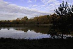 Vijver in de herfst met zonsopgang over achtergrond van bevroren water, bomen in November-kleuren met blauwe hemel en wolk stock foto