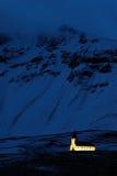 Vik Church i Island Nattfoto med ljuskyrkan och mörker - blått snöig berg Vinterplats från kalla Island Lös naturintelligens Royaltyfri Foto