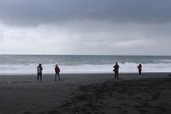 Vik Iceland, Maj, - 09 2018: Turyści podziwia ampułę machają zawalenie się na czarnej piasek plaży vik Obrazy Royalty Free