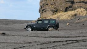 Jeep Wrangler on Icelandic terrain. VIK, ICELAND - MAY 03, 2018. Jeep Wrangler Unlimited Sport four wheel drive vehicle being used on terrain on a black sand stock footage