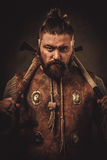 Viking with axes in a traditional warrior clothes royalty free stock image