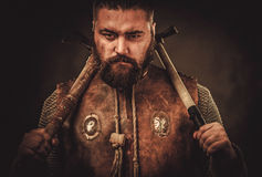 Viking with axes in a traditional warrior clothes stock photography