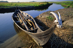 Viking boat. Replica of a traditional Viking boat accostée on a small river in Denmark Royalty Free Stock Image