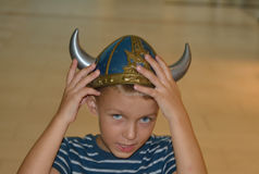 Viking boy with the hands on the helmet Royalty Free Stock Photos