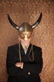 Viking Businessman. Businessman in dark suit and viking helmet stock photo
