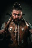 Viking with cold weapon in a traditional warrior clothes Stock Images