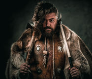 Viking with cold weapon in a traditional warrior clothes Stock Photo