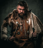 Viking with cold weapon in a traditional warrior clothes Royalty Free Stock Photos