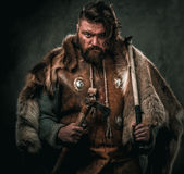 Viking with cold weapon in a traditional warrior clothes. Angry viking with axe in a traditional warrior clothes, posing on a dark background royalty free stock photography