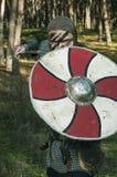 Viking, das Klinge und Schild auf dem wilden Naturhintergrund hält Lizenzfreies Stockfoto