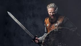 Viking dressed in Nordic armor holds a shield and silver sword. Artistic portrait of Scandinavian Viking dressed in Nordic armor holds a shield and silver sword stock photo