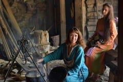 Viking-Frau bereitet Lebensmittel im Topf auf dem Feuer zu Stockfoto
