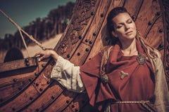 Viking-Frau, die nahe Drakkar auf der Küste steht Stockbild