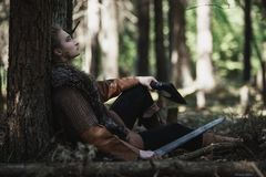 Viking-Frau mit der Klinge, die traditionellen Krieger trägt, kleidet in einem tiefen mysteriösen Wald lizenzfreies stockfoto
