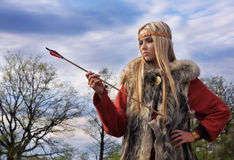 Viking girl with arrow. Viking girl warrior with the arrow on a sky backround Royalty Free Stock Photography